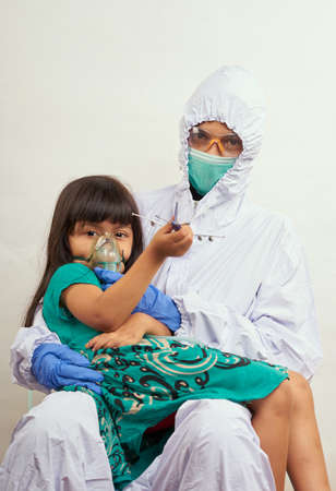 Female doctor in protective suit takes examining sick little girl, Coronavirus pandemic Concept
