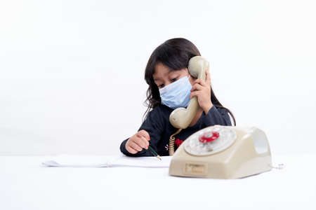 Cute little girl wearing face mask writing and study while talking on the phone