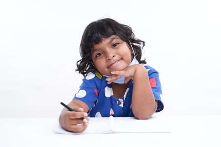 Little Schoolgirl Sitting At A Desk And Working On Her Homework, home education concept