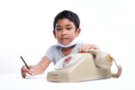 Young boy Talking on vintage telephone and making notes during online class at home Stockfoto - 161211353