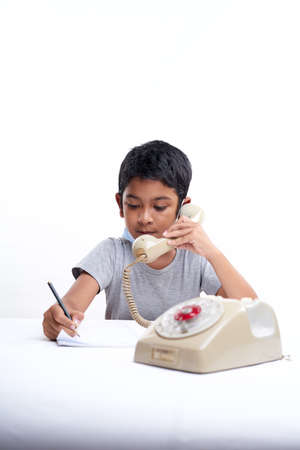 Young boy Talking on vintage telephone and making notes during online class at home
