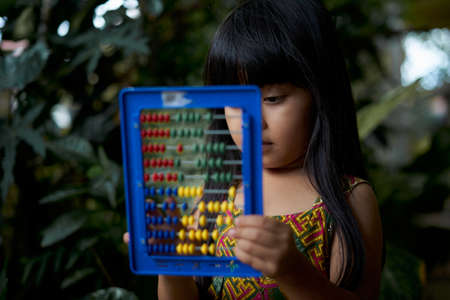 Cute little girl learn counting and Mathematics using abacus at park, Homeschooling education concept
