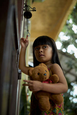 Little Girl and her tedy bear doll playing the Bell at home Stockfoto