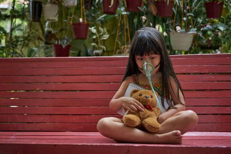 little girl with inhalation mask holding a notebook and teddy Bear doll