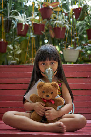 little girl with inhalation mask holding a notebook and teddy Bear doll Stockfoto - 161504194