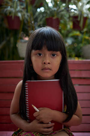 Pretty little girl holding a book and pencil and sitting in the backyard