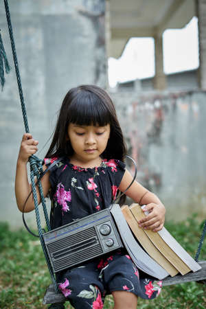 Cute Little girl covering head with book after study at the garden Stockfoto