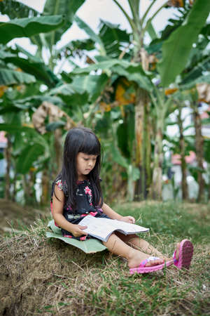 Girl reading a book and studying outdoors in the public park in summer