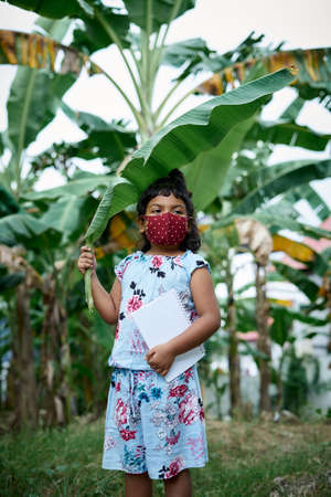 Little schoolgirl wearing face mask and covering head with banana leaf going to school