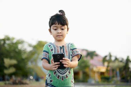Portrait of cute little girl using smartphone in the public park