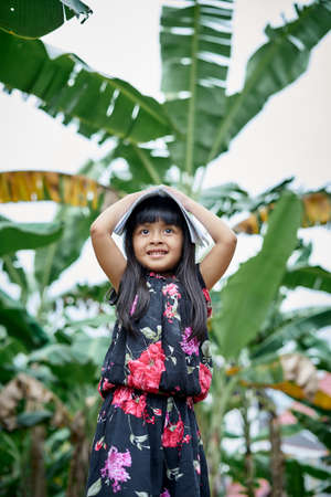 Portrait of cute girl having fun after study and reading a book at home garden, home schooling concept Stockfoto
