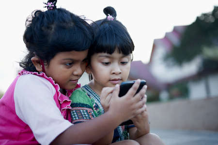 Two little Girls playing and learning with their smartphone at public park. Children and technology in pandemic new normal concept