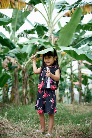 Little girl with banana leaf umbrella and holding a note book playing at park