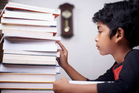 Little schoolboy study hard with stack of books at home