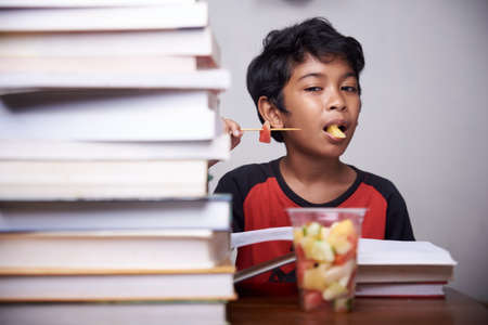Little boy eating mixed fruit after study at home