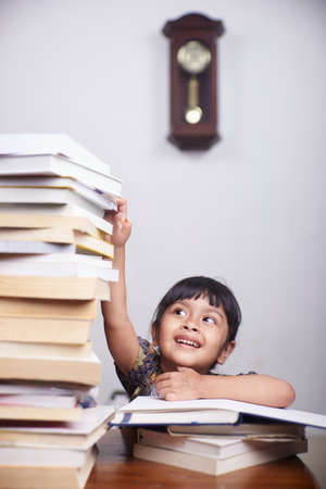 Happy little girl With Dark Hair Reading stack of Book In Library