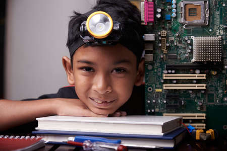 Little boy holding the motherboard, studying computer component at home