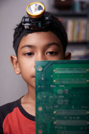 Little asian schoolboy repairing computer motherboard at home