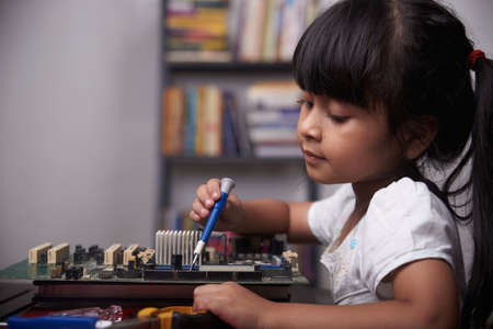 Little cute girl playing with broken computer part, kids creativity study at home during pandemic
