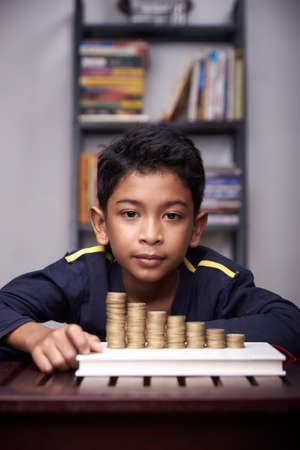 Young Schoolboy is counting his coins for education and business