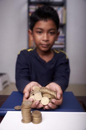 Asian boy saving money for education