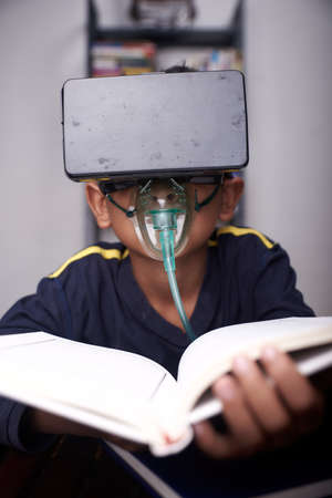 little Boy wearing VR headset and nebulizer mask studying at home quarantine