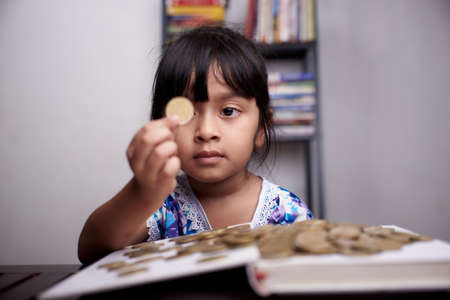 Little cute Girl is counting bunch of coins Stockfoto