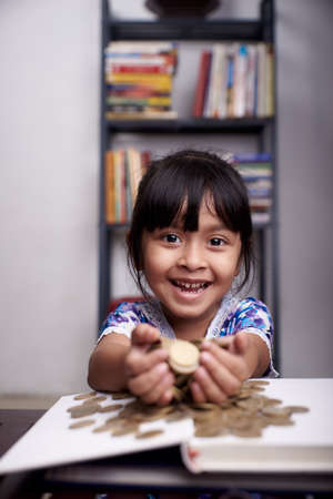 Pretty little Girl holding bunch of gold coins