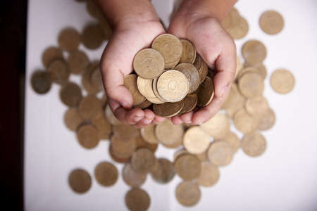 Children hand holding bunch of coins. Charity concept