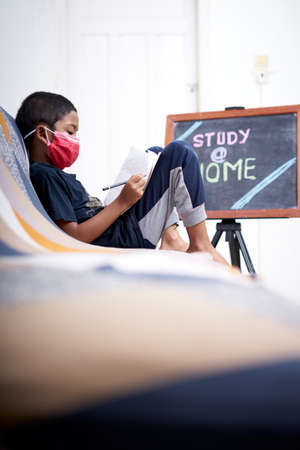Asian Boy with protective mask study at home due to the quarantine and lockdown situation.  preventive protocols in Indonesia Stockfoto