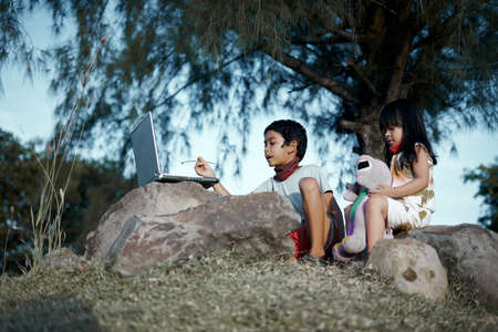 Little Boy and girl in face mask using laptop and studying under the tree at public park