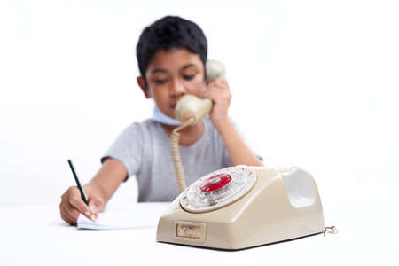 Schoolboy Talking on the telephone during online class at home