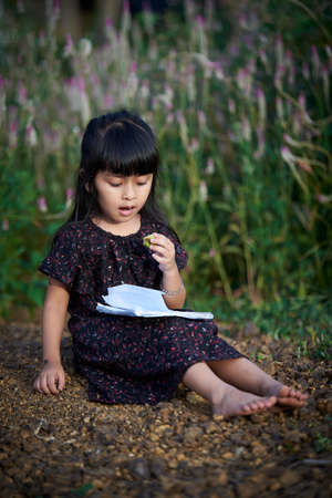 Little girl reading a book and sitting while eating fruit