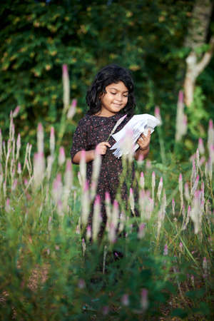 Asian schoolgirl reading a book and playing alone at natural park