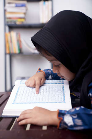 Asian Little girl reading Koran after praying at home