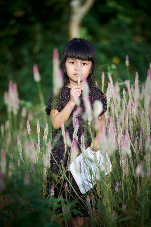 Cute little girl enjoying bloom of wild flowers in the field of meadow