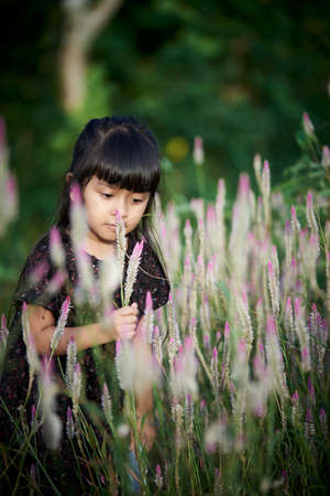 little asian girl playing with wild flowers at public garden