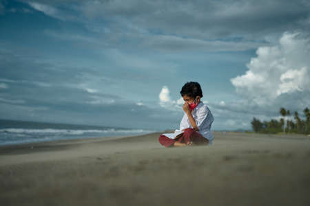 Schoolboy in medical mask reading a book on the beach Stok Fotoğraf