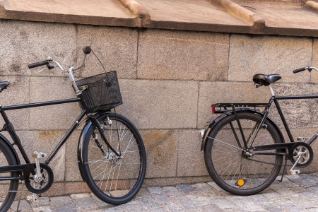 dynamo: Two old classic bicycles near the stone wall