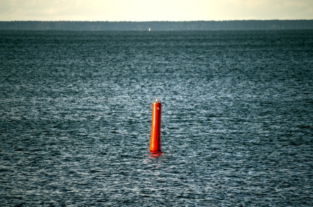 Blue steel water before storm with red buoy photo