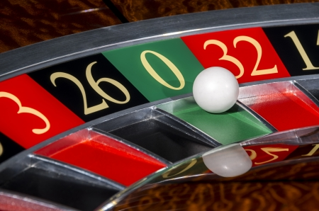 Classic casino roulette wheel with sector zero and white ball photo