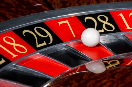 roulette table: Classic casino roulette wheel with red sector seven 7 and white ball and sectors 18, 29, 28, 12