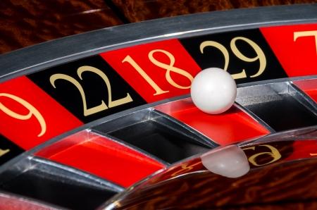 ruleta de casino: Casino clásico rueda de la ruleta con el sector rojo de dieciocho 18 y la bola blanca y los sectores 9, 22, 29, 7 Foto de archivo