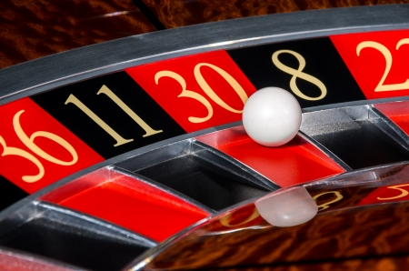 Classic casino roulette wheel with red sector thirty 30 and white ball and sectors 36, 11, 8, 22