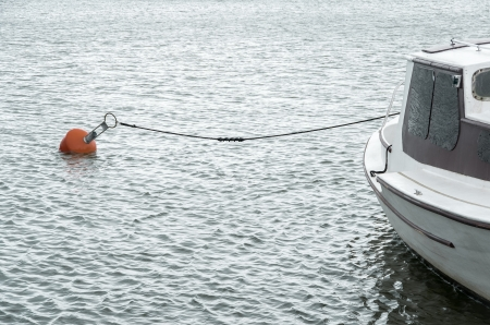 White boat on water in harbour with floating red buoy and black rope photo