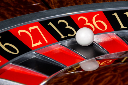 Classic casino roulette wheel with black sector thirteen 13 and white ball and sectors 6, 27, 36, 11 Stock Photo