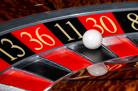 Classic casino roulette wheel with black sector eleven 11 and white ball and sectors 13, 36, 30, 8