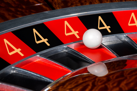 Concept of classic casino 4 lucky numbers roulette wheel with black and red sectors and white ball
