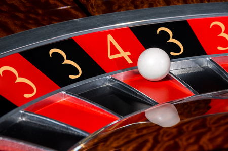 wheel spin: Concept of classic casino code 3-3-4-3-3 lucky numbers roulette wheel with black and red sectors and white ball Stock Photo
