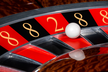 bola ocho: Concept of classic casino code 8-8-2-8-8 lucky numbers roulette wheel with black and red sectors and white ball Foto de archivo